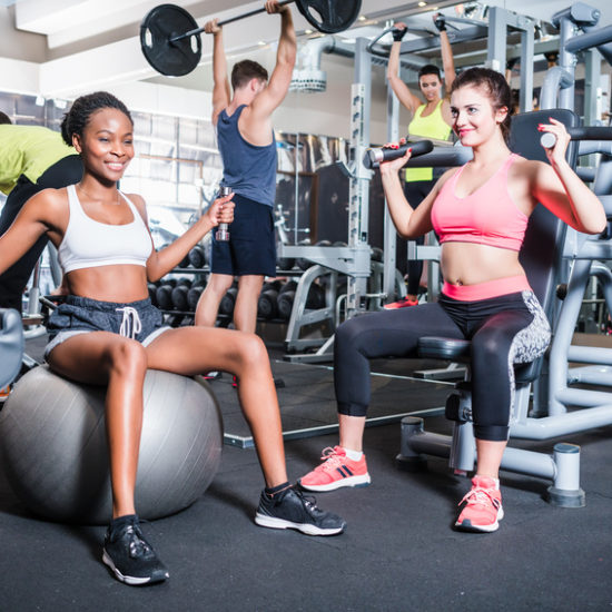 Woman and men having fun doing fitness sport in gym